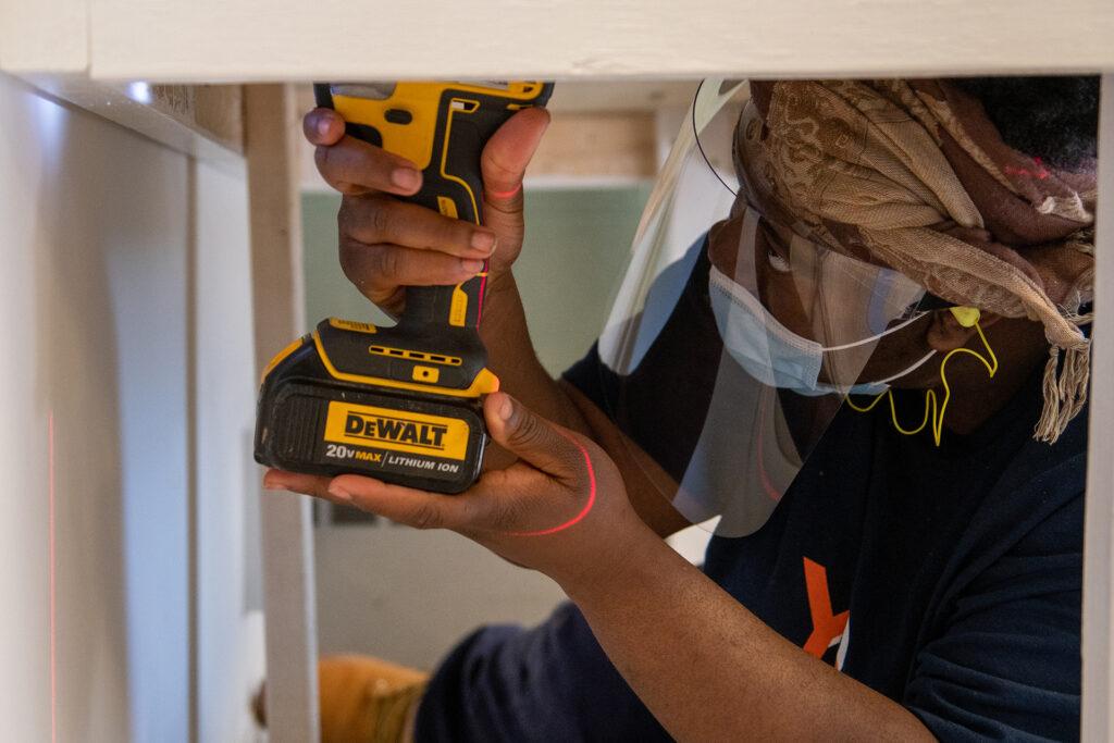 Student drills under a desk